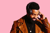Portrait of a smiling man with beard and headphones, looking down listening to music, isolated on pink studio background