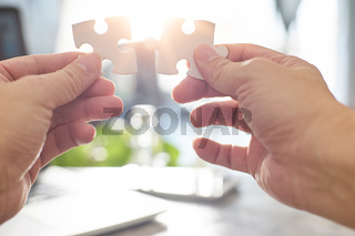 Young businessman trying to connect couple puzzle piece with sun flare and blur background
