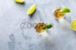 Golden tequila shots with limes and salt rims, shot from the top with a place for text