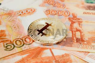 Close-up of Bitcoin coins on 5000 Russian rubles banknote. Crypto currency BTC.