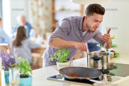 Junger Mann mit Kochlöffel am Herd als Hobbykoch
