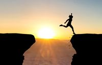 Woman landing after jumping over abyss in front of sunset.