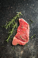 Raw veal schnitzel. Raw meat and rosemary