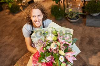 Lächelnder Florist mit buntem Blumenstrauß