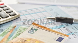 Some euro bills on documents with a calculator