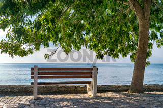 A bench and a tree against the see in Nessebar ancient city on the Bulgarian Black Sea Coast in Nessebar. Calm, relaxation, vacation concept