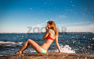 Pretty girl in a bikini beside the ocean laughing as she is splashed by a wave crashing on the rocks.