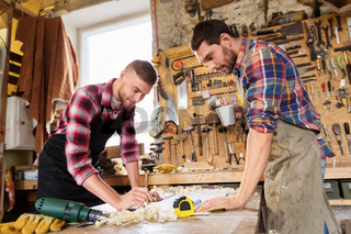 carpenters with ruler and coffee at workshop