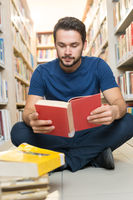 Handsome young student sitting on library floor reading book in college