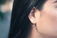 Right ear with hanging earring with red gemstone of a brunette woman. Close up