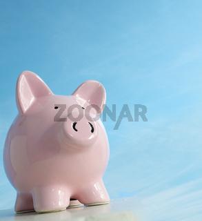Piggy bank on blank blue background