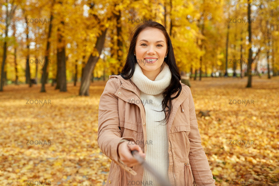 woman taking picture by selfiestick at autumn park
