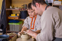 Potter showing how to work with ceramic in pottery studio