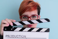 redhead woman holding movie  clapper on cyan background