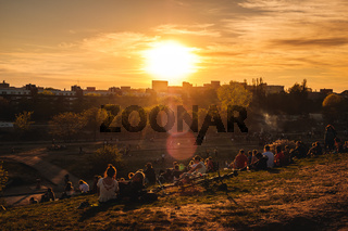 People enjoying sunset, outdoor in public park (Mauerpark) on summer day in Berlin
