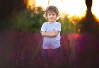 Handscome boy standing in red wildflowers. Serious face and curly hair.