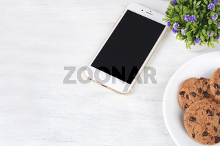 Empty screen mobile with plastic cup of coffee and cookies
