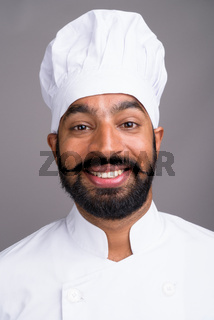 Face of young handsome Indian man chef smiling