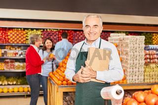 Lächelnder Senior als Verkäufer mit Klemmbrett