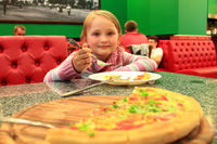 Little girl eating pizza in pizzeria. Big pizza and girl. Delicious fast food meal