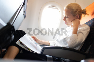 Woman reading in flight magazine on airplane. Female traveler reading seated in passanger cabin. Sun shining trough airplane window