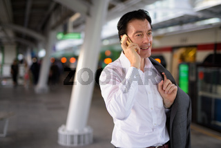 Mature handsome businessman talking on phone outdoors