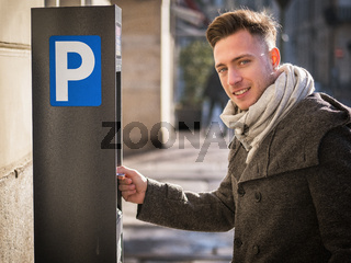Young man paying for a parking ticket at machine