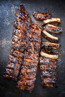 Barbecue spare ribs St Louis cut with hot honey chili marinade as top view on a rusty board