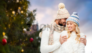 happy couple hugging over christmas tree