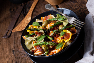 Pasta salad with green asparagus, olives and parma ham