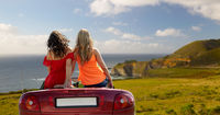 friends driving in convertible car over big sur