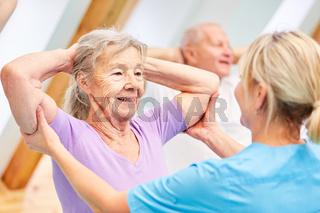 Trainer hilft Seniorin beim Rückentraining