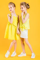 The girls of the twins stand together on a yellow background.