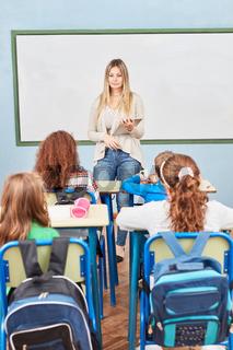 Lehrerin mit Tablet PC vor ihrer Klasse