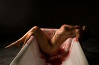 Nude brunette bleeding in bath shot
