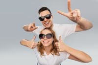 happy couple in sunglasses showing peace