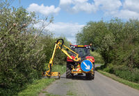 Grass verges being cut by tractor mower.