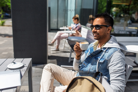 indian man drinking coffee at city street cafe