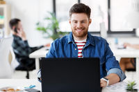 smiling creative man with laptop working at office