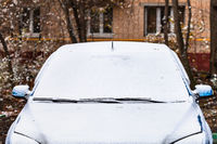 first snow on car in front of apartment house