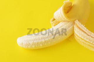 Peeled banana on yellow background
