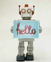 robot toy holding a  hello sign