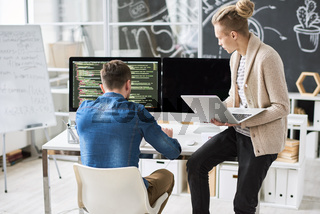 Development team discussing computer code
