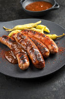 Traditional barbecue German Bratwurst with hot sauce and peperoni as closeup on a modern design cast iron plate