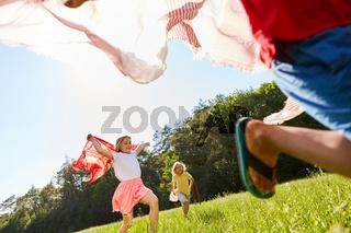Kinder spielen und laufen mit Tüchern