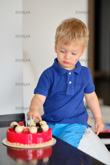 Boy trying birthday cake