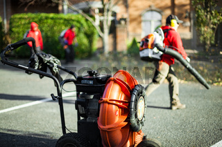 Team of workers blowing leaves with blower in the front