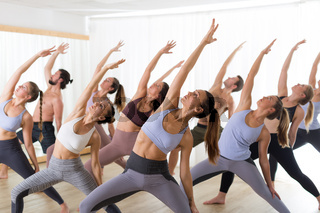 Group of young sporty attractive people in yoga studio, practicing yoga lesson with instructor, stretching on floor in Trikonosana, triangle yoga pose. Healthy active lifestyle, working out in gym.