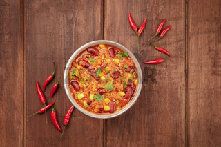 Chili con carne, a Mexican stew with red beans, meat, and chili peppers, shot from above on a dark rustic wooden background