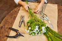 Hände von Floristin beim Blumen binden mit Bast